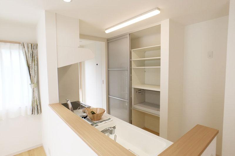 キッチンの後ろには標準装備の扉付の食器棚。家電も食器も全て収納できる。
